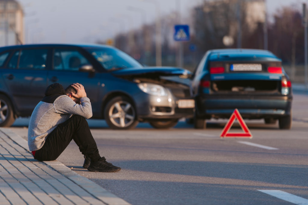 A man sits outside a car accident